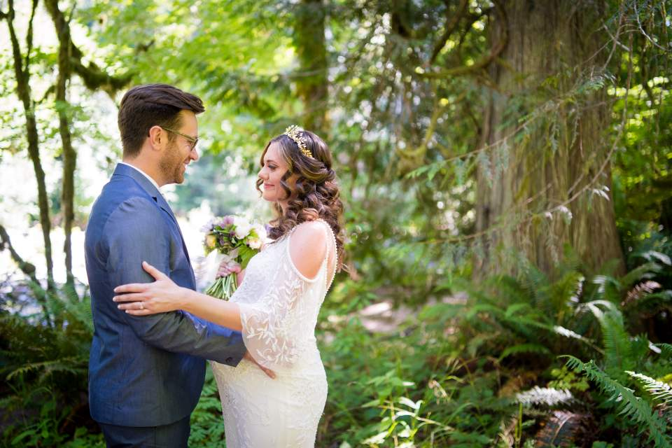 bride and groom embrace in forest at treehouse point fall city washington