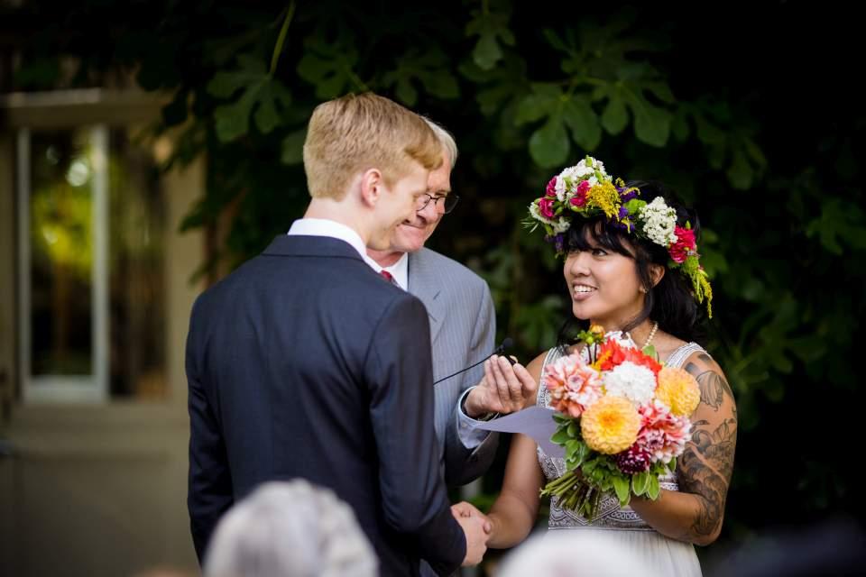 bride and groom exchanging vows corson building