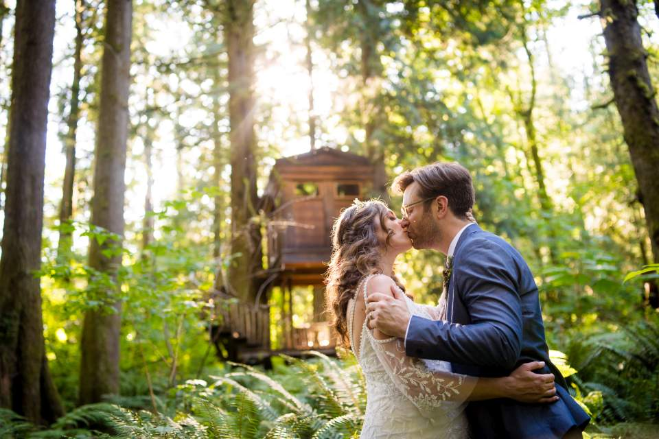 bride and groom kissing under treehouse