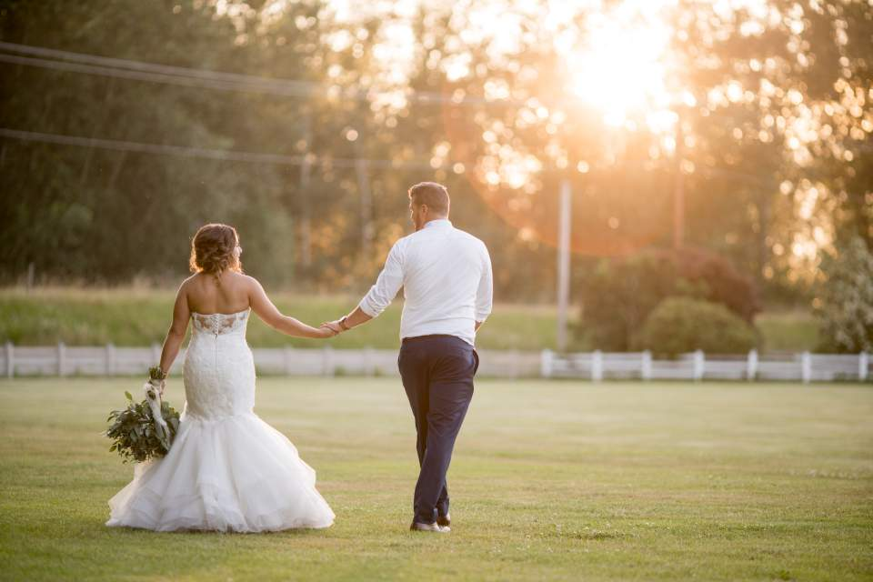 bride and groom walking through field together
