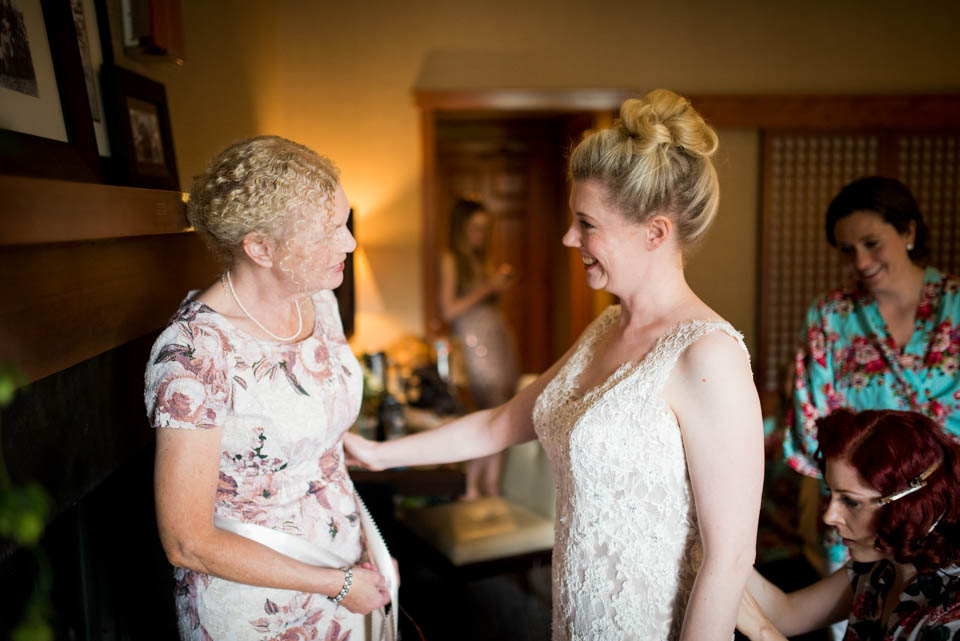 bride and mom sharing a wedding day moment getting ready