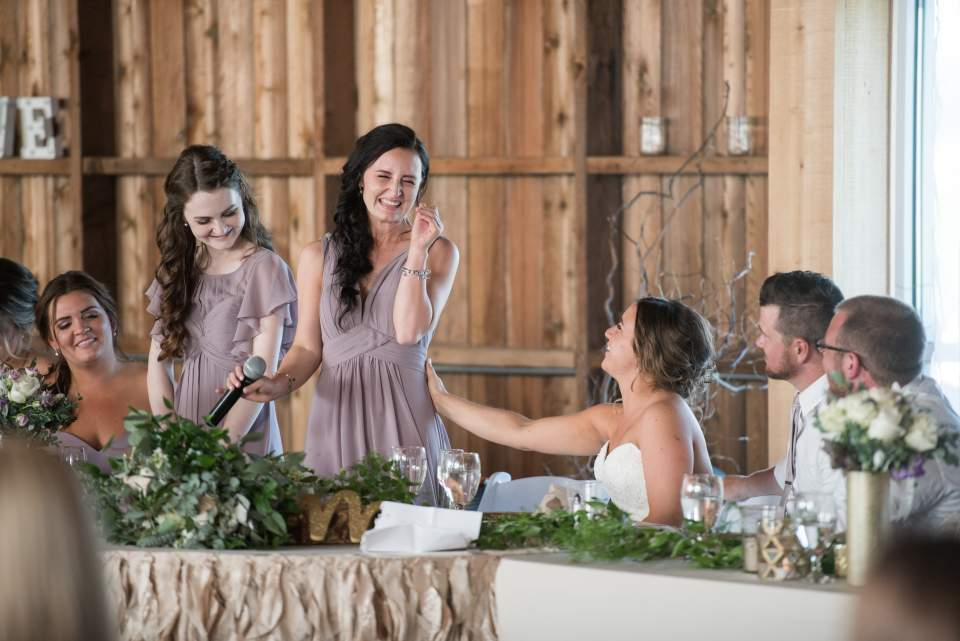 bride consoling crying bridesmaid during wedding speech