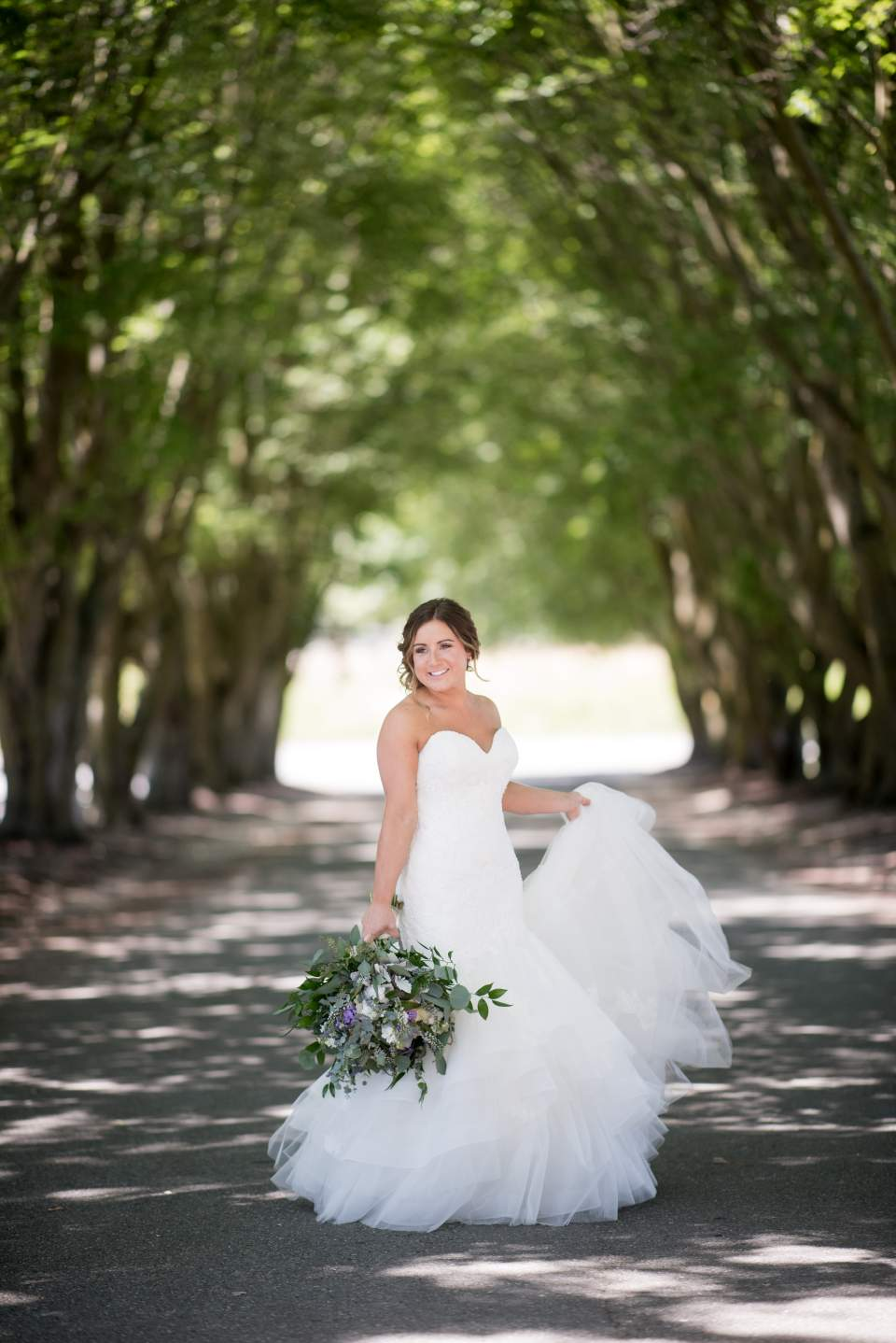 bride twirling wedding dress in a row of trees
