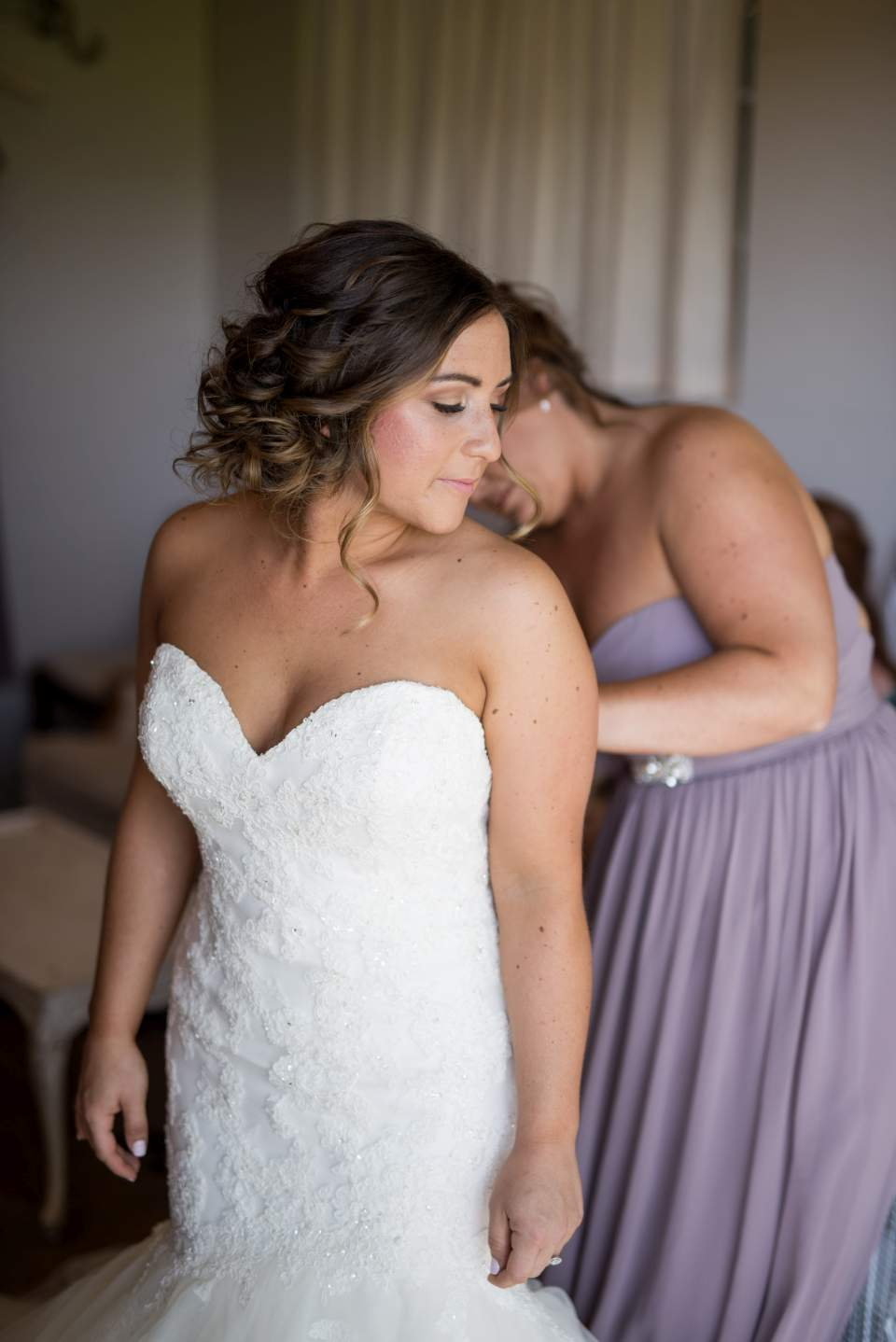 bride waiting as her wedding dress is zipped up