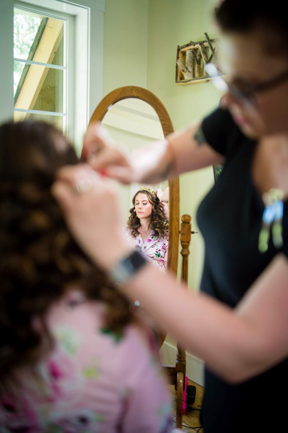 bride watching in mirror as hair styists puts boho crown on