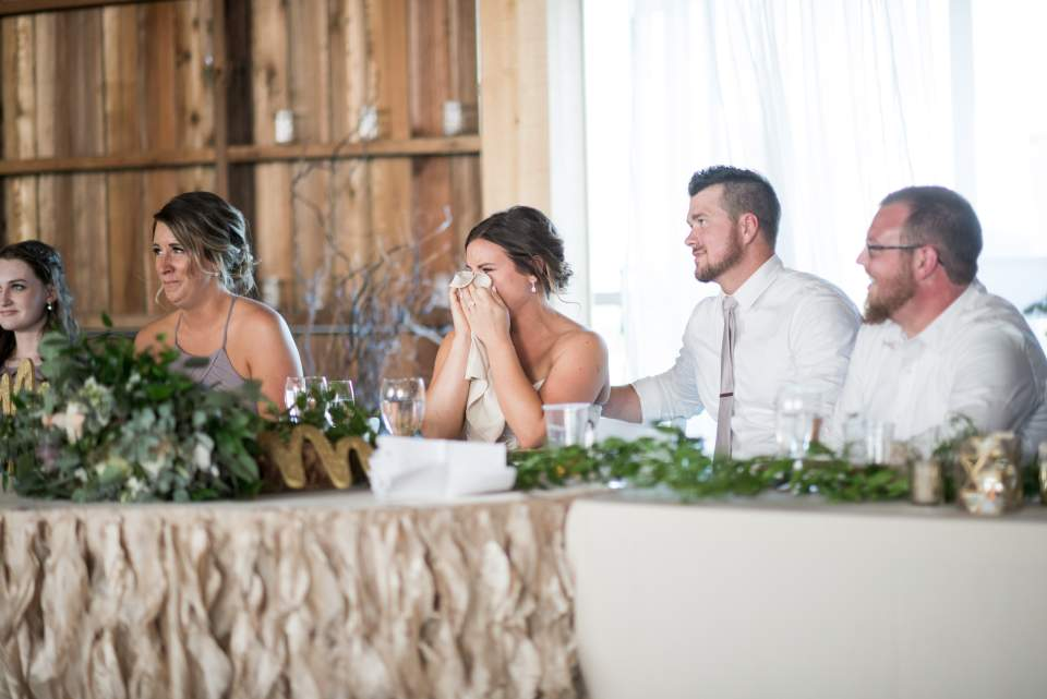 bride wiping tears during toasts