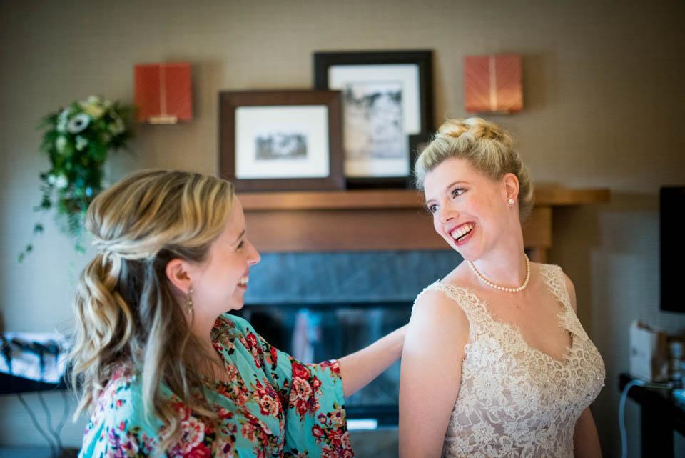 bridesmaids admiring wedding dress photos