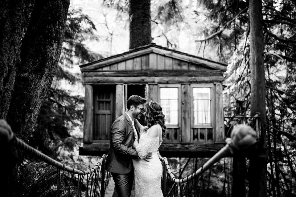 couple kissing in front of temple of the blue moon treehouse at tree house point wedding
