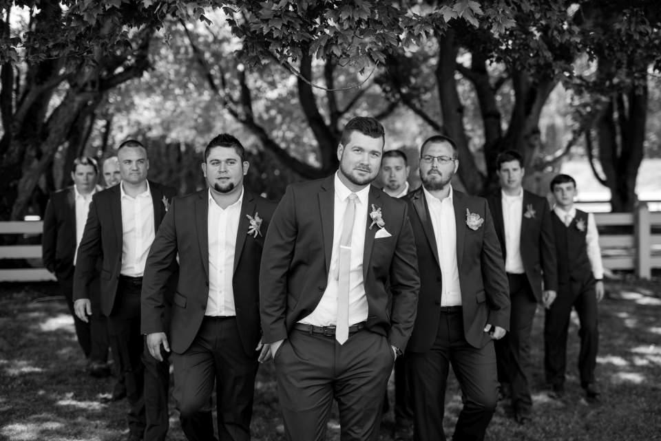 dapper groomsmen walking towards camera