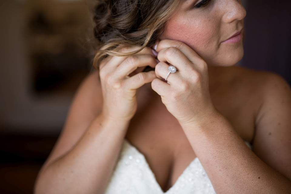 detail photo of bride putting in earrings