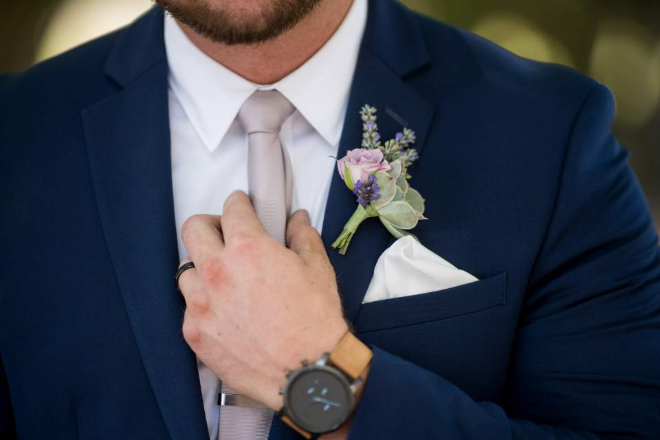 detail photo of groom fixing tie and bout