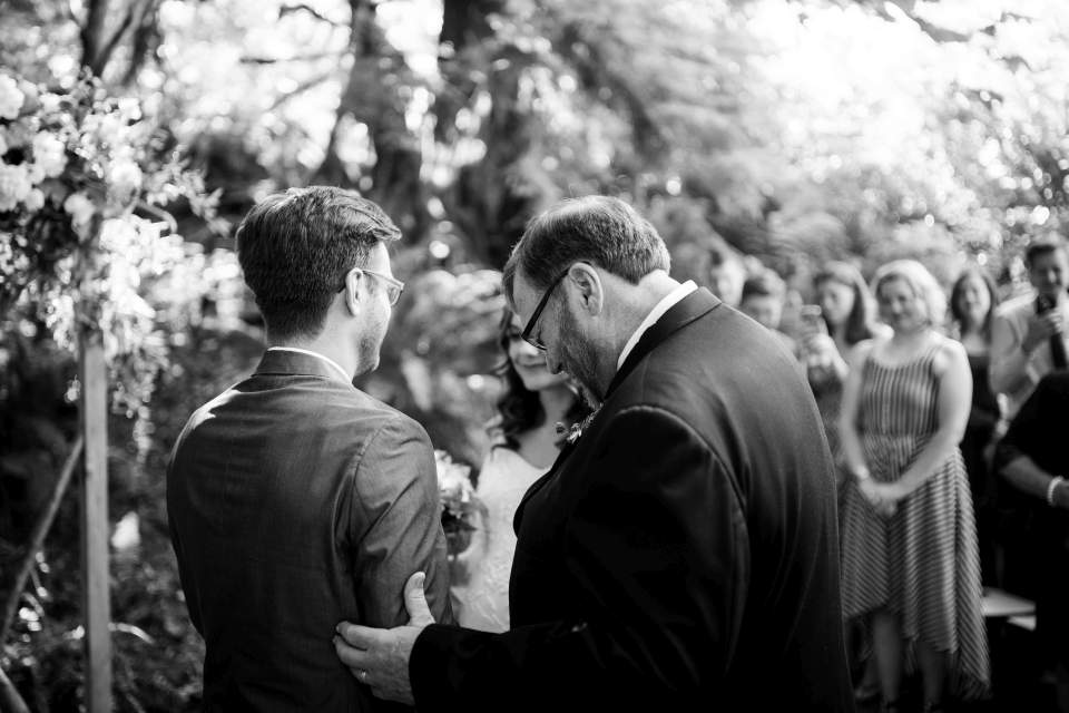 father of the bride handing her off to groom during wedding ceremony