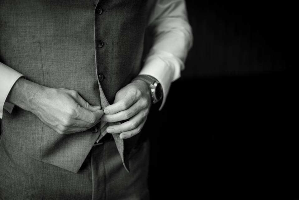 groom buttoning vest in the morning