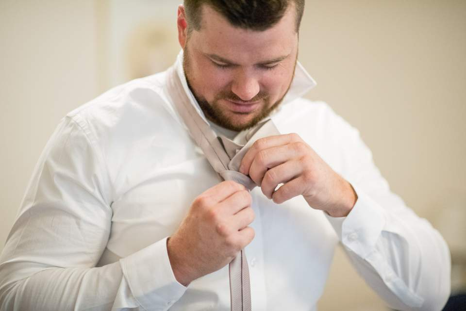 groom tying his tie getting ready for wedding