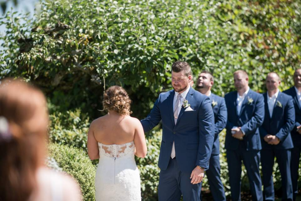 groom watching bride read vows to him