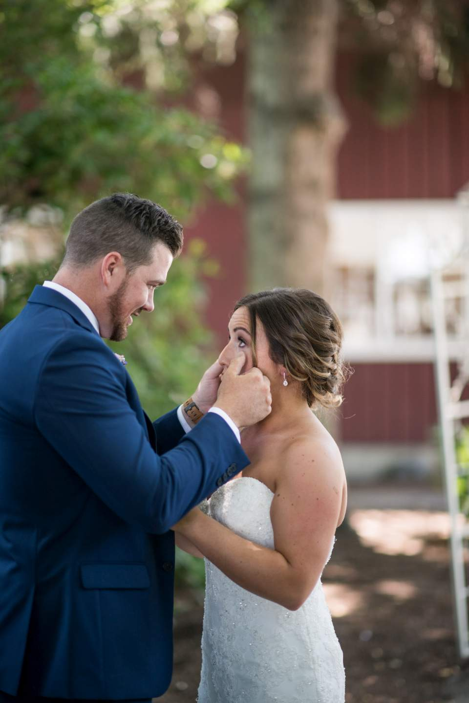 groom wiping tears from brides eyes on wedding day