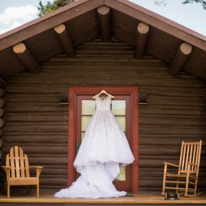 wedding dress in front of log cabin getting ready details