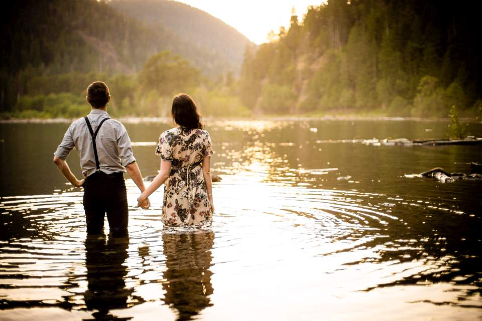 couple holding hands watching sunset over the lake in washington
