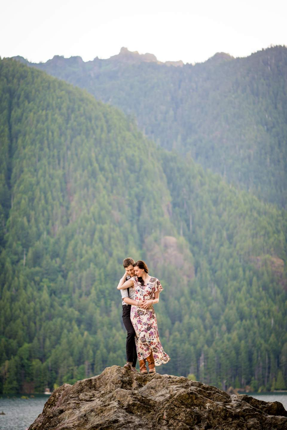 couple standing on a rock embracing with mountains behind them