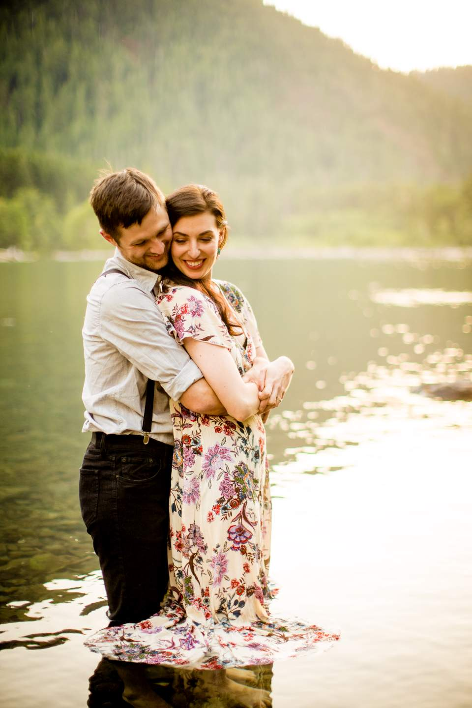 couple wading into lake for engagement photos