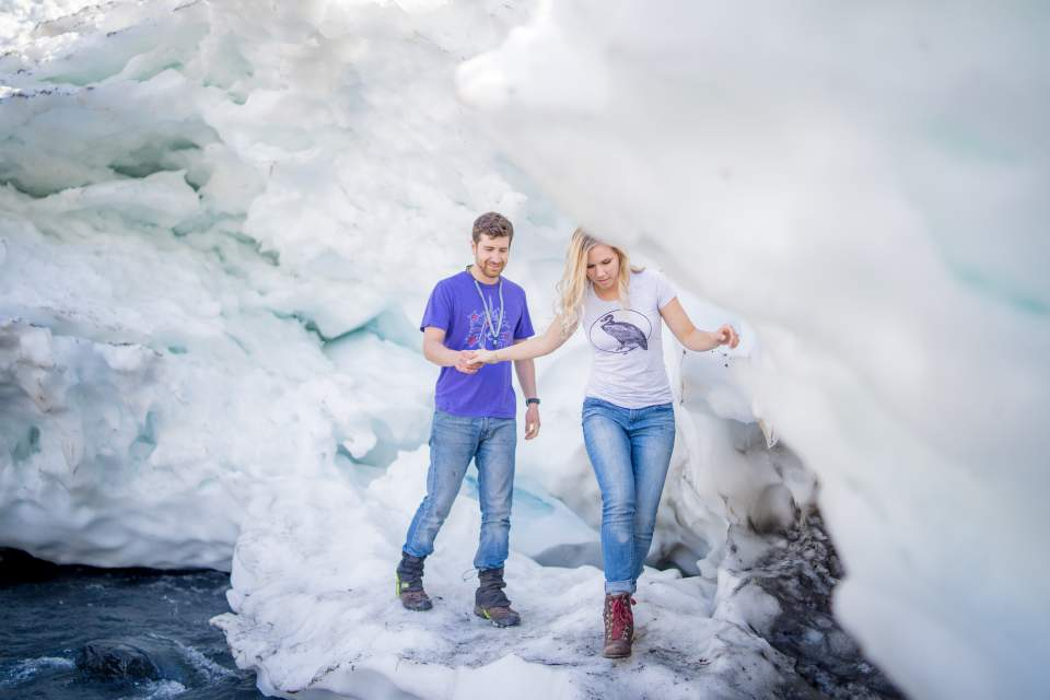 couple walking on glacial ice