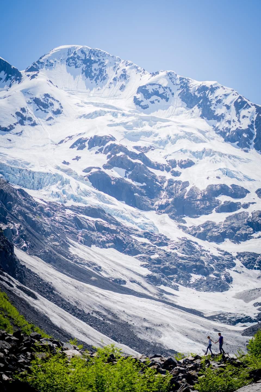 couple walking together across mountain backdrop