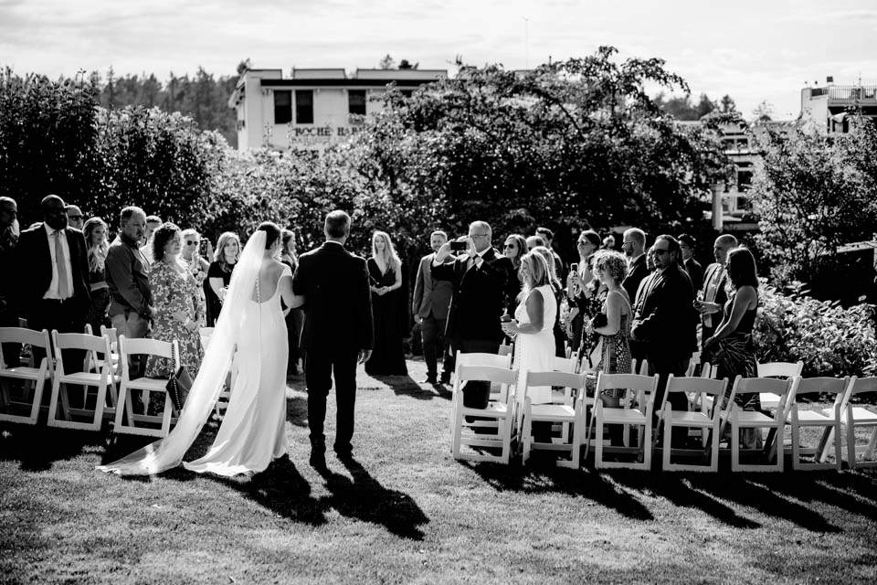 black and white of bride and father walking down aisle at roche harbor