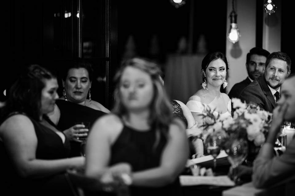 black and white of bride watching toasts