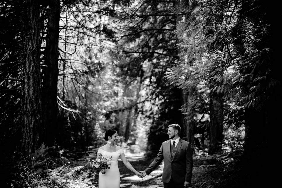 black and white of couple holding hands in woods