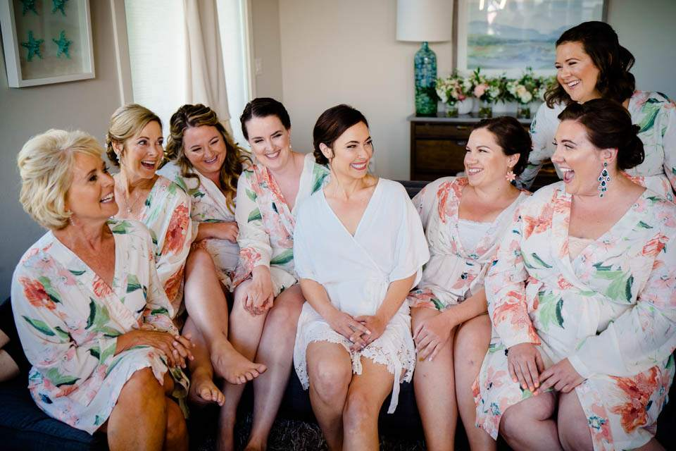 bride and bridesmaids in robes sitting on couch