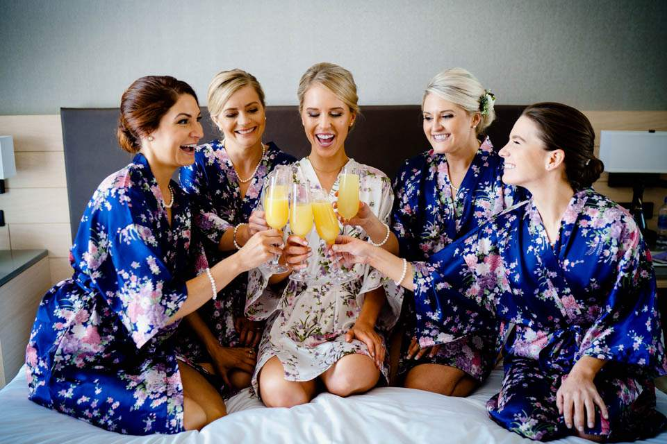 bride and bridesmaids toast with mimosas on bed in downtown seattle hotel