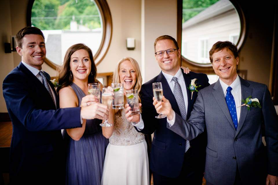 bride and groom cheers with officiant and wedding party