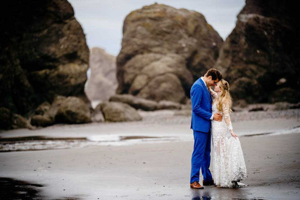 bride and groom embrace on ruby beach