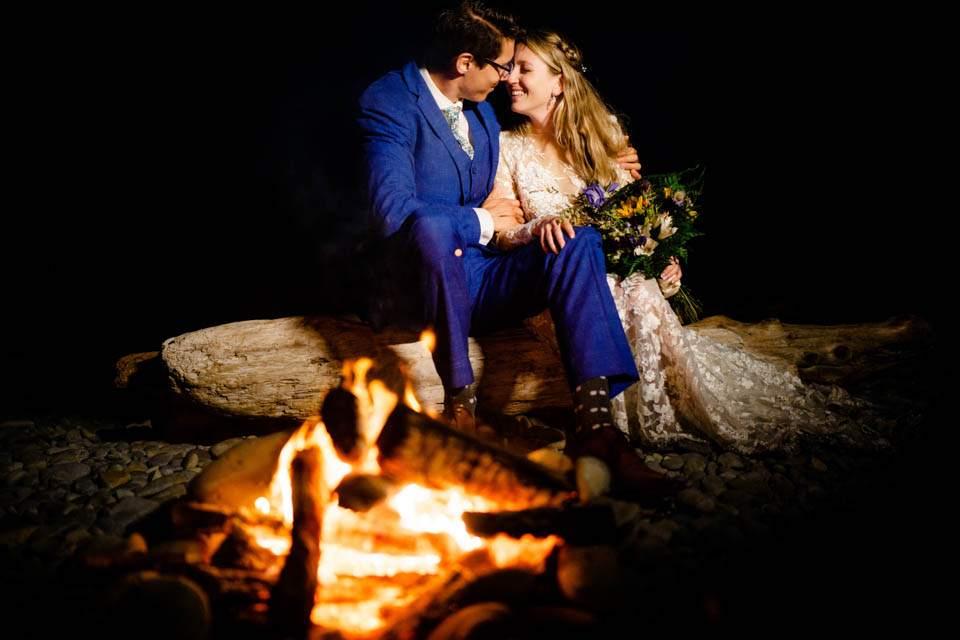 bride and groom keeping warm by beach fire