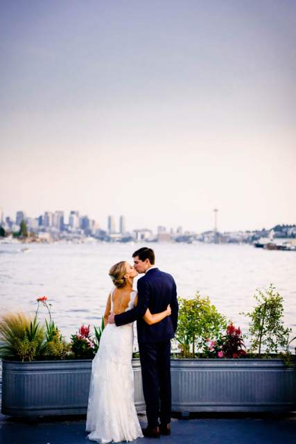 bride and groom kiss in front of seattle skyline from mv skansonia