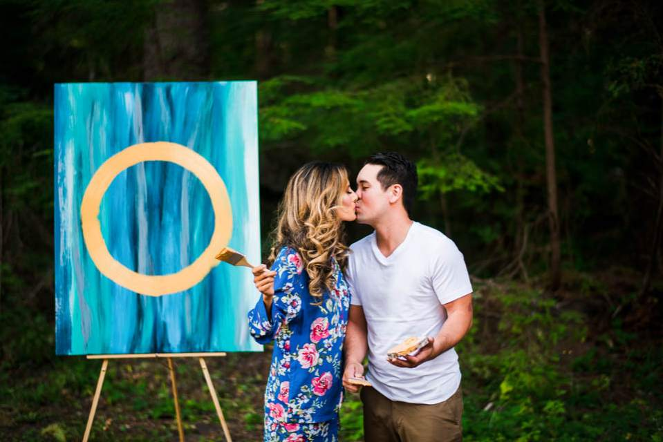 bride and groom kiss in front of unity painting