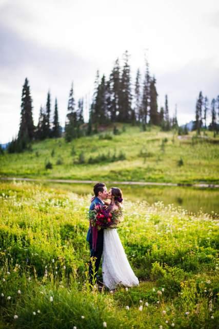 bride and groom kiss in wildflowers