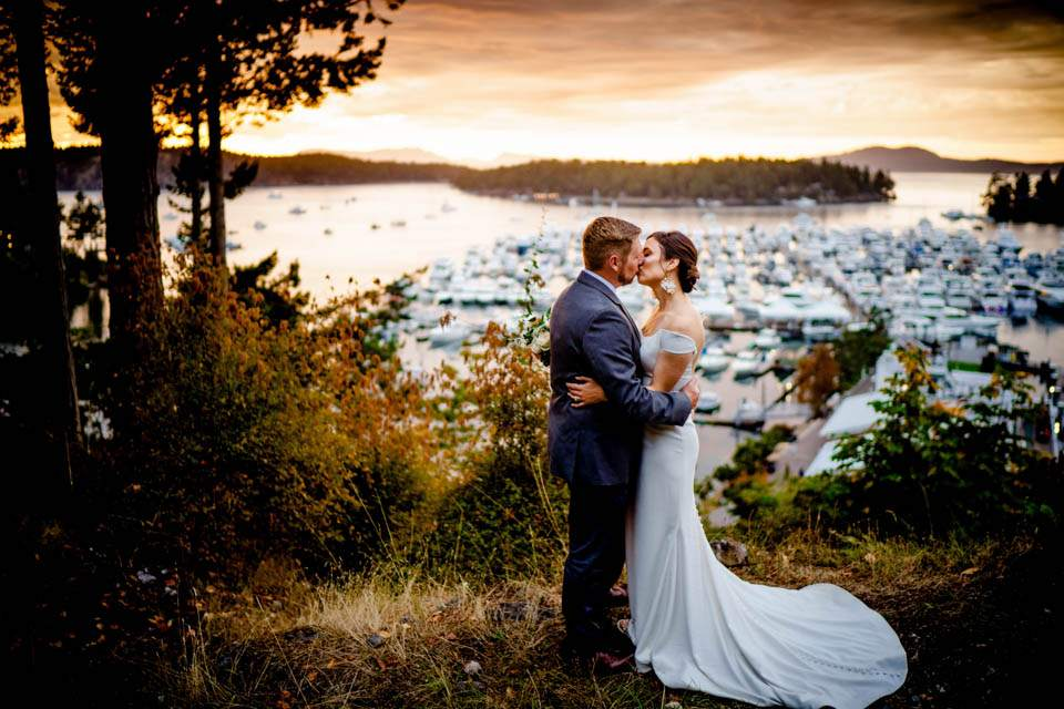 bride and groom kiss with roche harbor in background