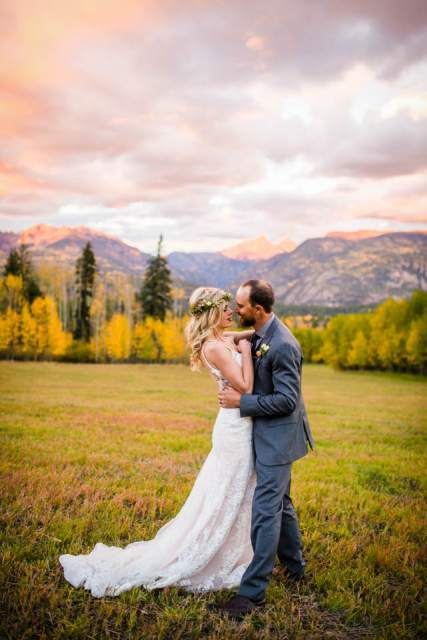 bride and groom kissing in mountains at sunset