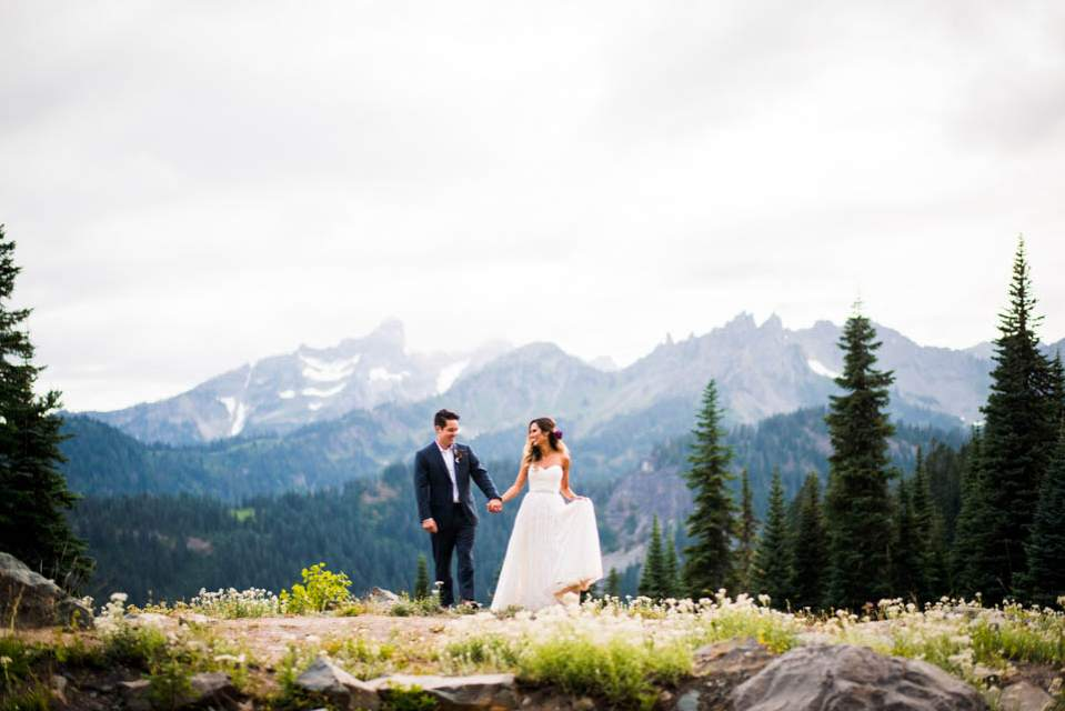 bride and groom walking across mountains