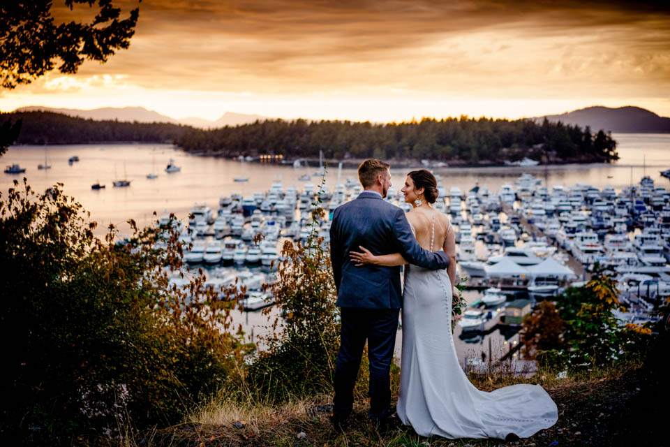 bride and groom watching sunset on their wedding day at roche harbor washington