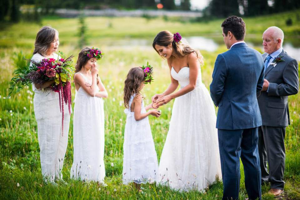 bride getting ring from flower girl
