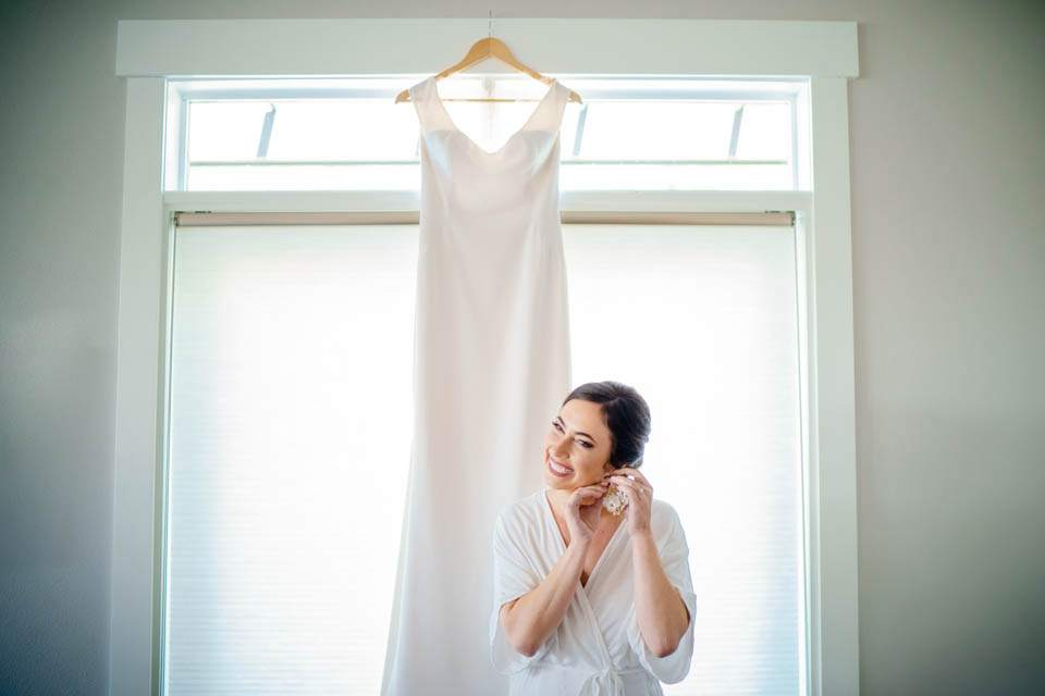 bride puts earrings on in front of wedding dress hanging in window