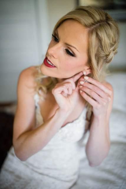bride puts wedding earrings on