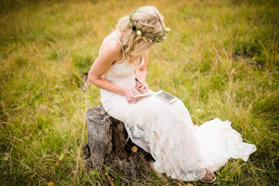 bride writing vows on a tree stump