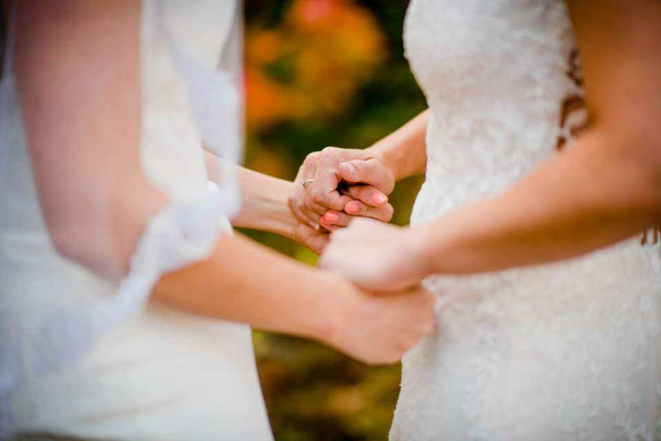 brides holding hands in wedding dresses 2