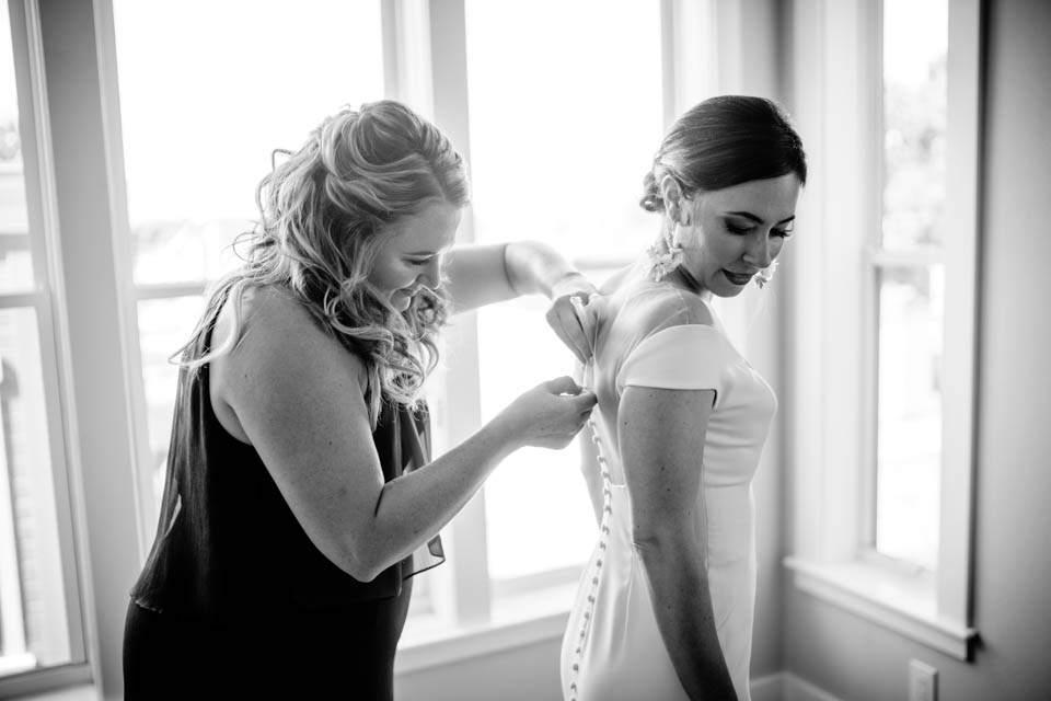 bridesmaid helping with brides dress