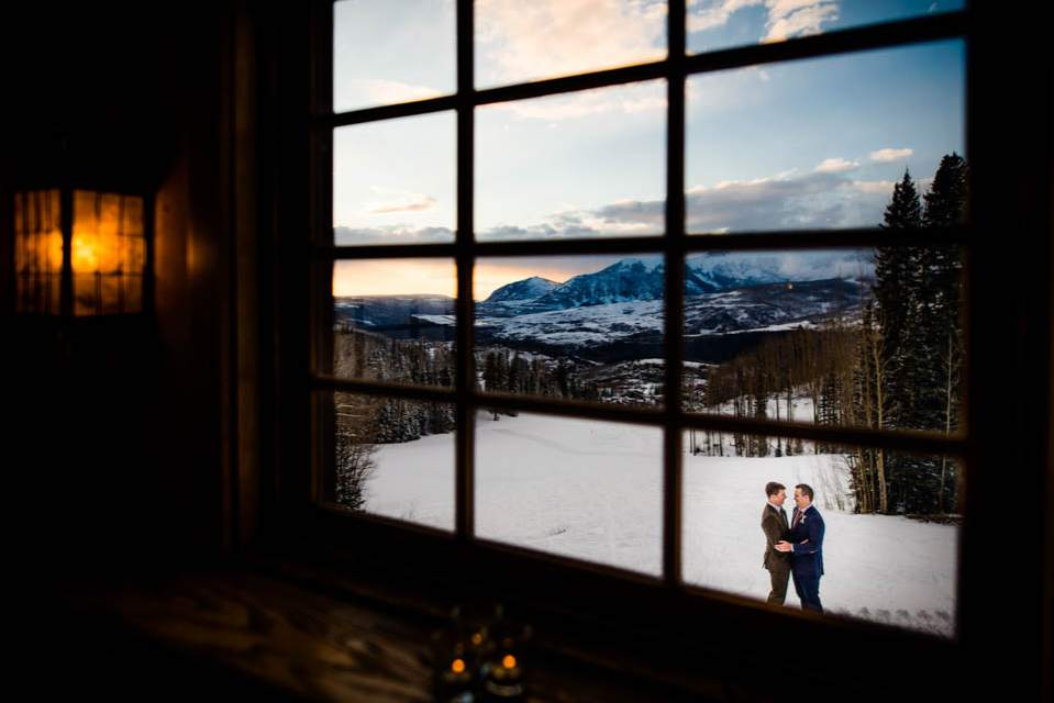 creative wedding photo through lodge window of grooms embracing in the mountains