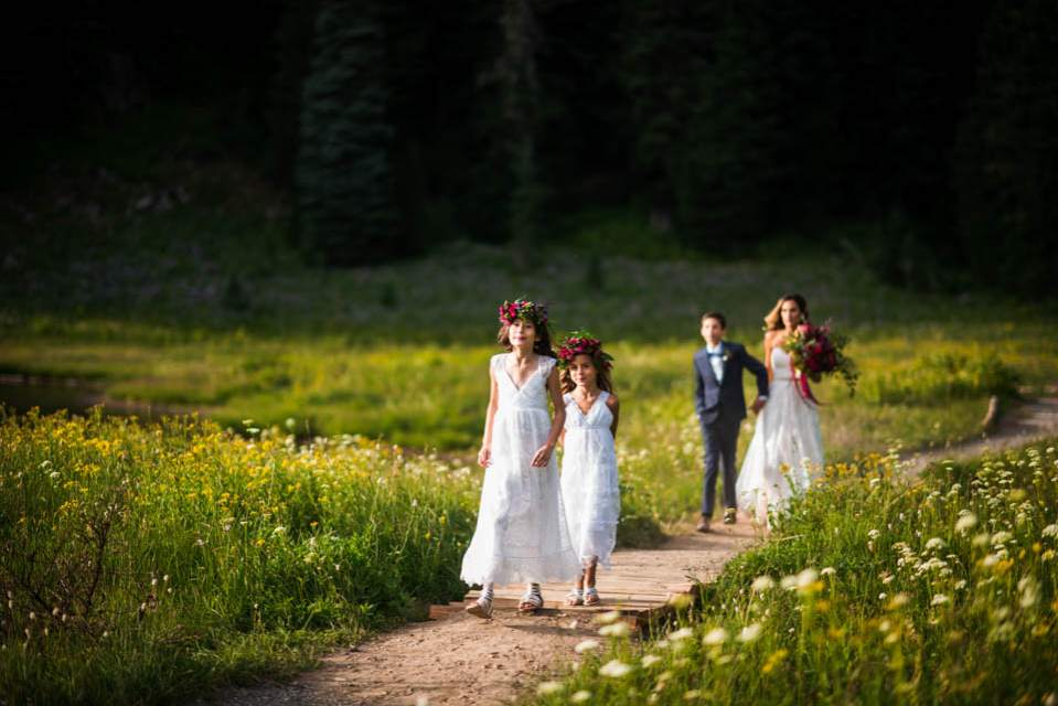 flower girls and bride walking down trail
