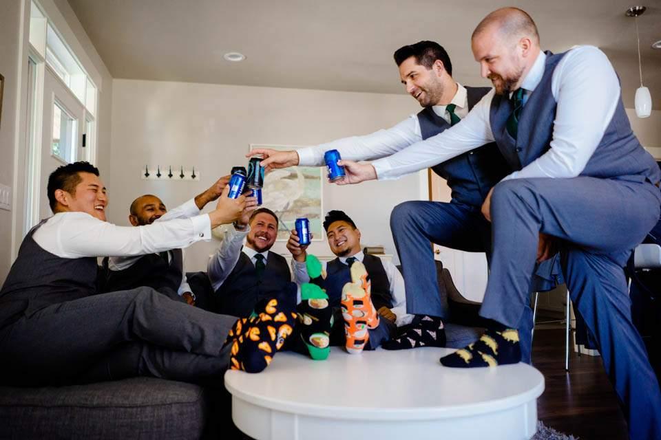 groom and groomsmen cheers with beers wearing fun wedding socks
